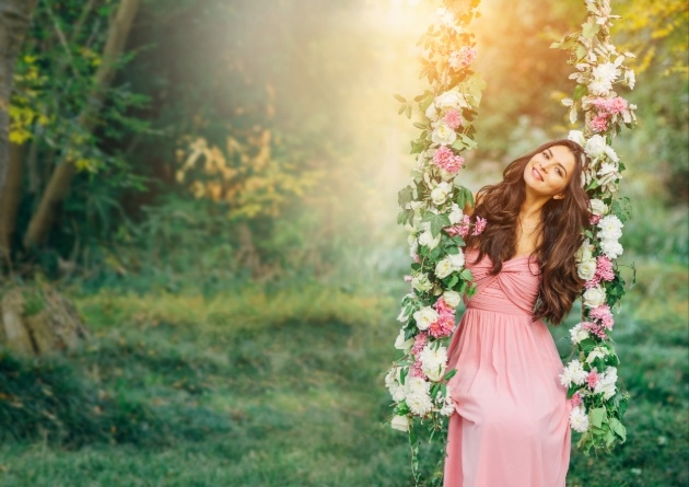 bride in a pink dress on a swing hanging from a tree branch