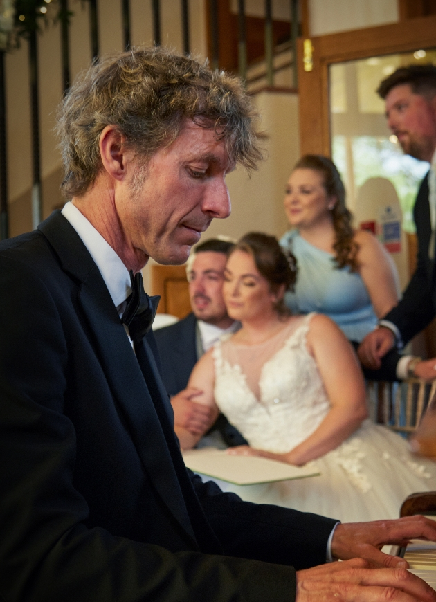 Paul Arnold playing the piano at a wedding
