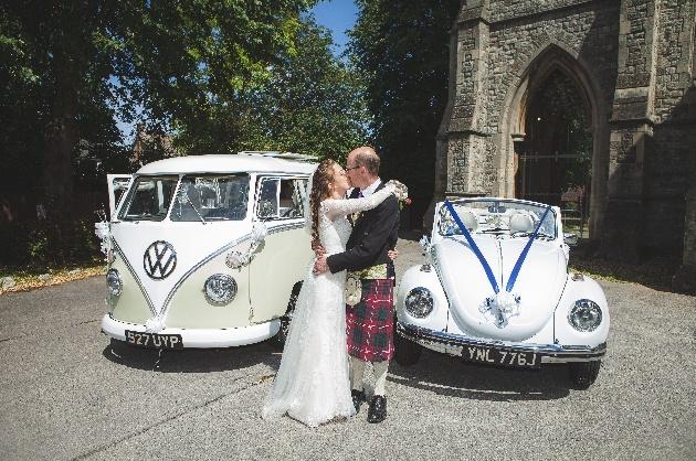 Couple kiss next to wedding cars