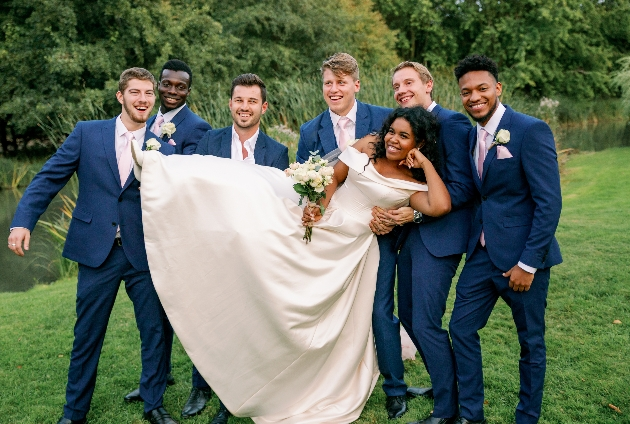Groomsmen carry bride