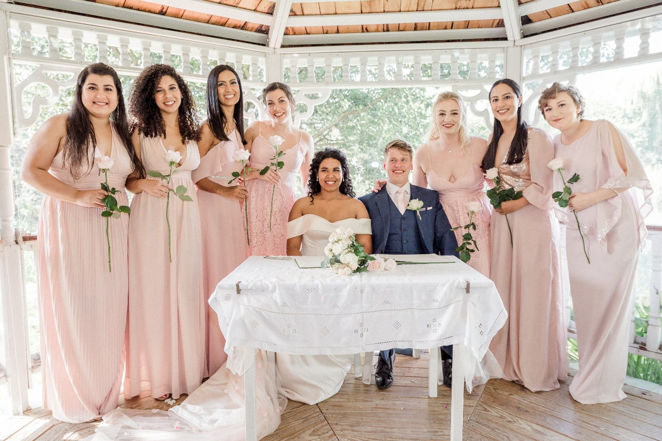 Bridesmaids pose with couple signing the register