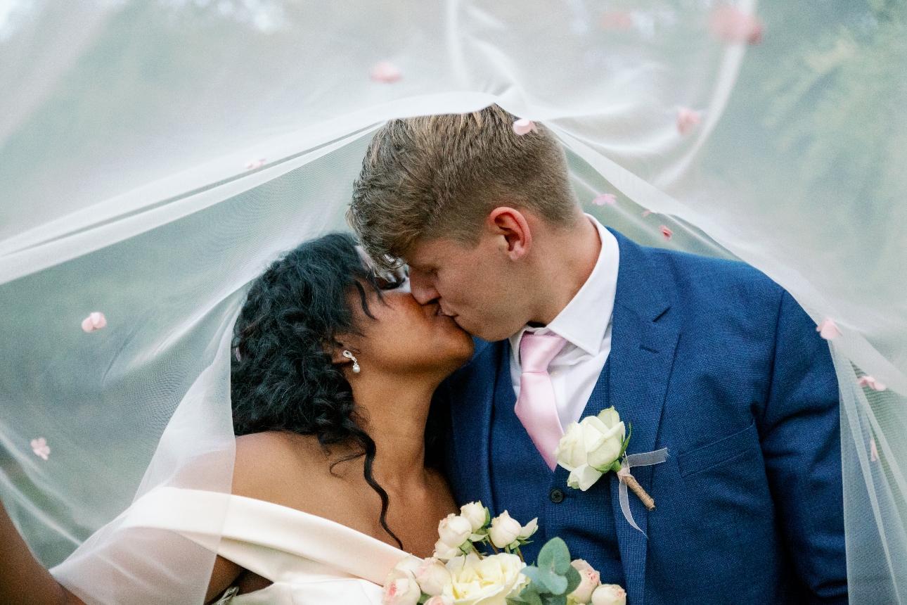 Couple kiss under bride's veil